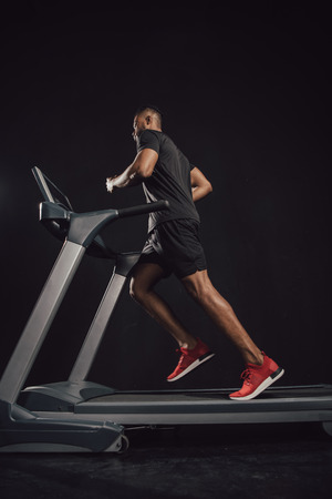 Low angle view of young African American sportsman running on treadmill on black background
