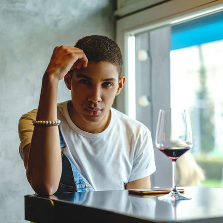 Attractive African American man sitting in cafe with glass of wine