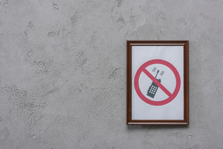 Frame with restricted phone placard on concrete wall background