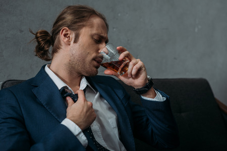 Young alcohol addicted businessman drinking whiskey Imagens