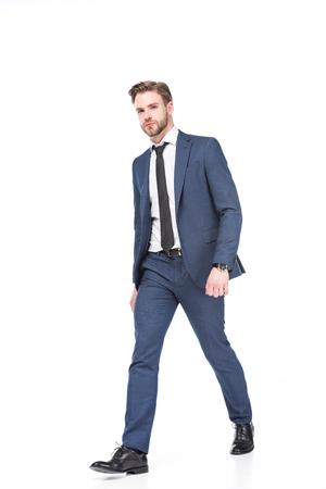 Hombre de negocios caucásico en traje caminando aislado sobre fondo blanco.