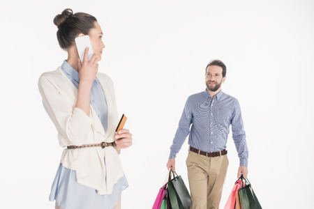 Woman with credit card talking on smartphone while husband carrying shopping bags isolated on white background Reklamní fotografie