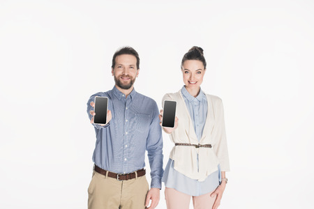Portrait of smiling couple showing smartphones with blank screens in hands isolated on white background