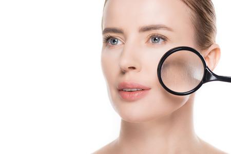 Vergrootglas op gezicht van vrouw met schone huid die op witte achtergrond wordt geïsoleerd
