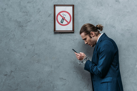 Depressed businessman in suit with hands tied with wire using smartphone under restricted smartphone sign, phone addiction concept