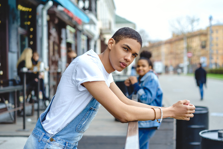 Stylish young man standing on city street