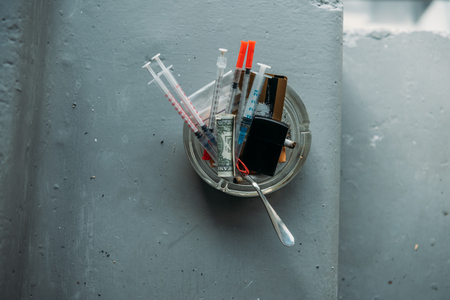 Top view of can with heroin syringes and various objects