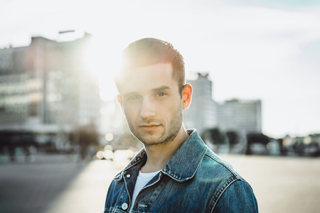 Confident young man in jeans jacket on city street Stock Photo