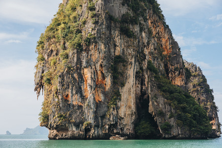 Beautiful scenic cliff with green vegetation in calm ocean at Krabi, Thailand