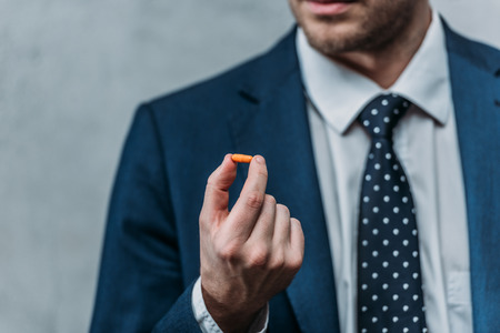 Cropped shot of addicted businessman holding drug pill