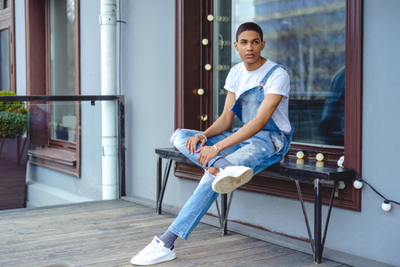 African American boy wearing casual clothes sitting on a bench by building in city