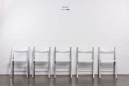 Close up view of arranged empty chairs in hall for visitors of job interview