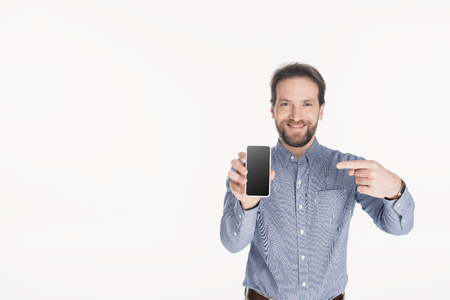 Portrait of smiling bearded man pointing at smartphone with blank screen in hand isolated on white background Imagens