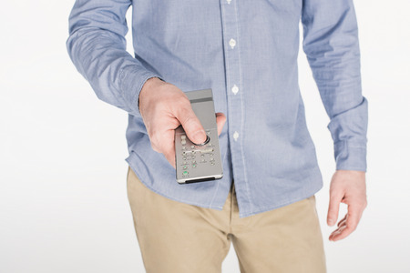 partial view of man holding remote control in hand isolated on white Stock Photo