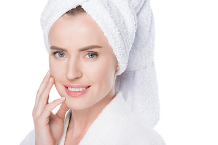 Woman with clean skin in bathrobe and towel on hair touching own face isolated on white background