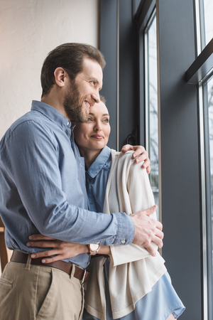 Portrait of beautiful smiling couple hugging each other and looking out window
