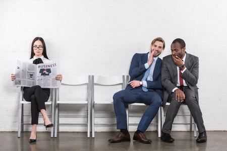Empresarios multiétnicos chismeando y empresaria asiática leyendo el periódico mientras esperan una entrevista de trabajo Foto de archivo
