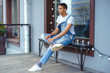 Thoughtful young man sitting on a bench by building in city Stock Photo