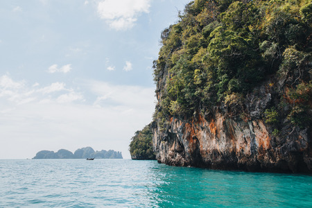 beautiful scenic rocks with green vegetation and calm transparent water at Krabi, Thailand