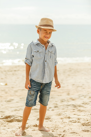 Adorable boy in hat winking at camera on beach