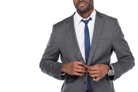 cropped shot of african american businessman buttoning suit isolated on white Stock Photo