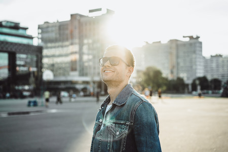 Smiling young man in sunglasses on city street Stock Photo