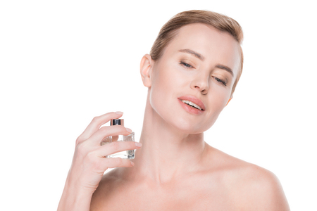 Woman with clean skin using perfume isolated on white