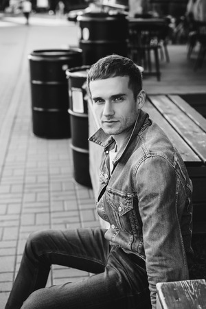 Black and white photo of young man wearing casual clothes sitting on bench