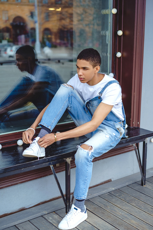 African american boy tying shoelaces on bench by window