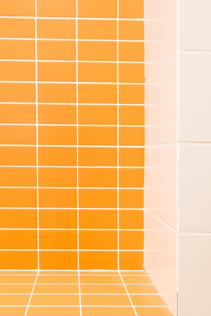 Close up view of white and orange tile in bathroom