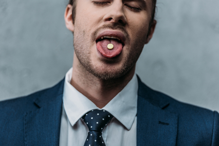 Close-up portrait of addicted businessman sticking out tongue with mdma pill