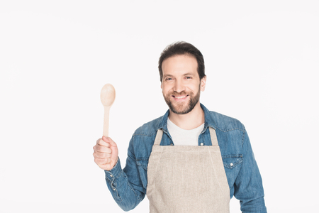 Portrait of smiling man in apron with wooden spoon isolated on white background