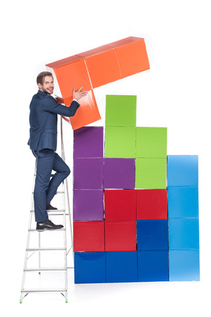 Businessman on ladder collecting colorful blocks isolated on white background Banco de Imagens
