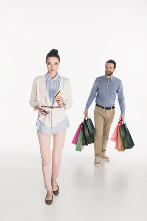 Woman with credit card and smartphone looking at camera while husband carrying shopping bags isolated on white background