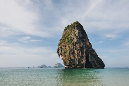 Scenic cliff with green vegetation in calm ocean at Krabi, Thailand Stock Photo