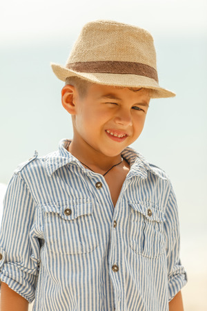 Close-up portrait of adorable boy winking at camera on beach 版權商用圖片 - 112003882