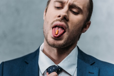 Close-up portrait of addicted businessman sticking out tongue with drug pill Stock Photo