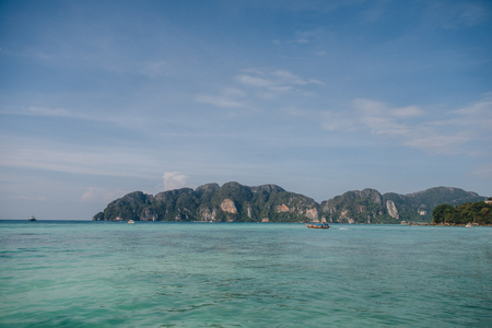 Beautiful cliffs and boats on calm water at Phi-Phi island, Thailand