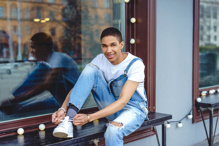 Smiling young man tying shoelaces on bench by window