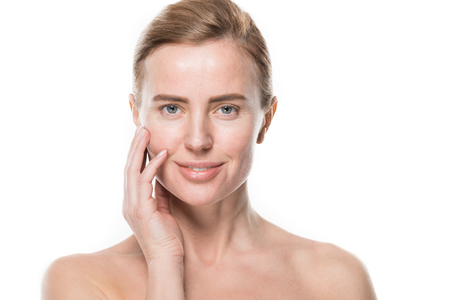 Woman with clean fresh skin touching own face isolated on white background