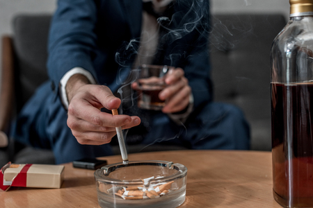 Cropped shot of businessman with glass of whiskey and cigarette 版權商用圖片