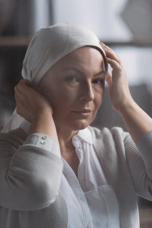 Close-up view of sick mature woman in kerchief looking at camera