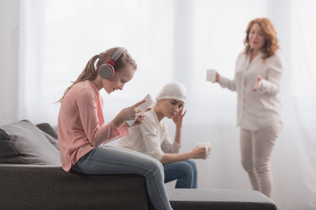 Child in headphones using digital tablet while sick mother and grandmother talking behind Stock Photo