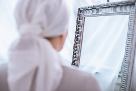 Back view of sick woman in kerchief standing near mirror, cancer concept Archivio Fotografico - 112044787