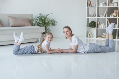 Relaxed mother and daughter lying on floor together and looking at camera