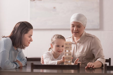 Family of three generations playing with wooden blocks together, cancer concept