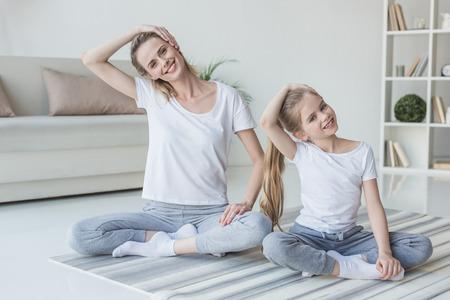 自宅で運動する前に首を伸ばす母と娘 写真素材