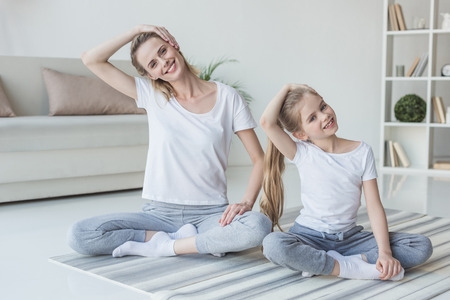 Mother and daughter stretching neck before exercising at home 版權商用圖片