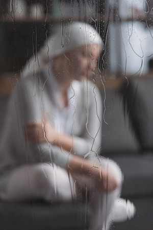 Close-up view of glass with raindrops and sick mature woman behind Stok Fotoğraf