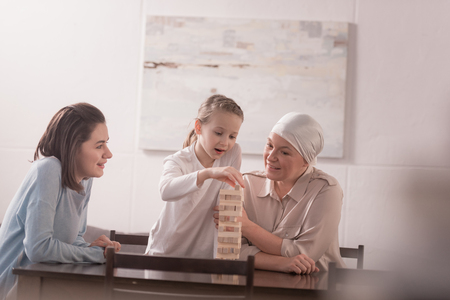 happy family of three generations playing with wooden blocks together, cancer concept Stock Photo